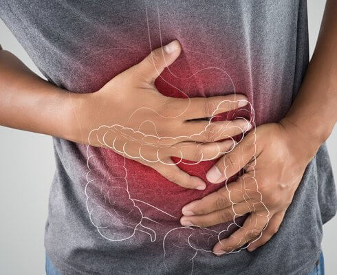 The photo of large intestine is on the man's body against gray background, People With Stomach ache problem concept, Male anatomy; blog: what is crohn's disease