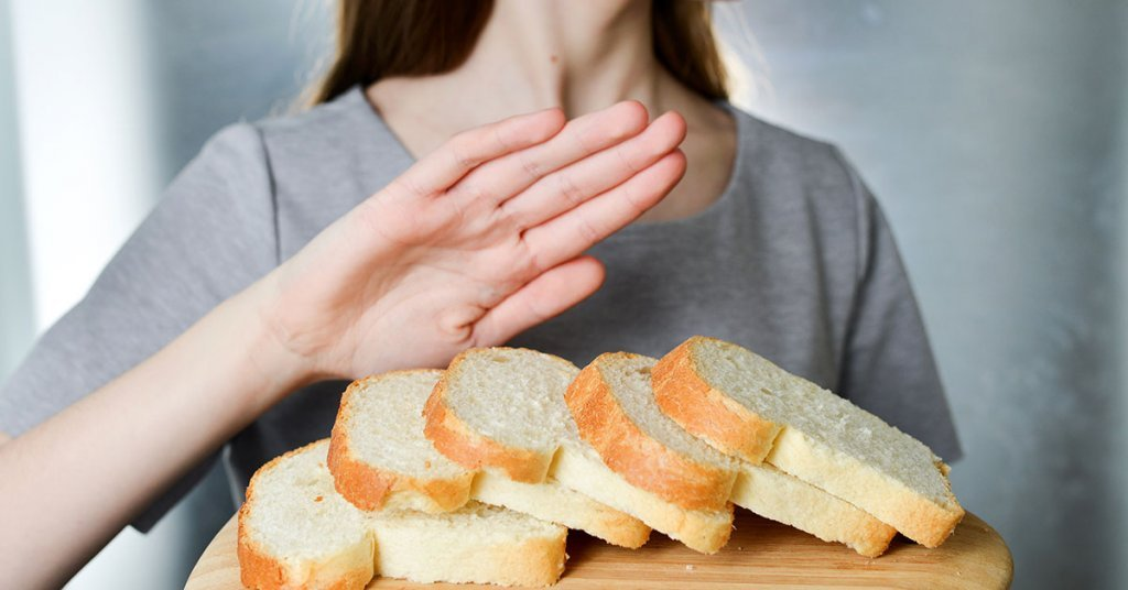 Gluten intolerance concept. Young girl refuses to eat white bread - shallow depth of field - selective focus on bread; blog: common signs of celiac disease